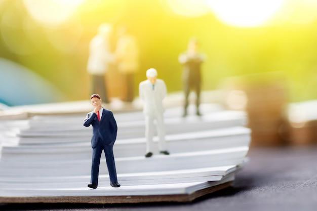Miniaturowe osoby: biznesmen stoi na schodach książki.