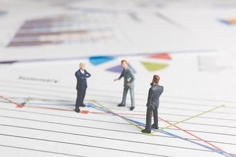 Miniaturowe osoby: biznesmen stojący na wykresie wykresu papieru
