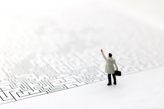 Miniaturowe osoby: biznesmen stojący na początku labiryntu.