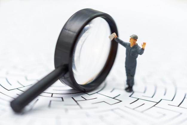 Miniaturowe osoby: biznesmen używa szkła powiększającego, aby znaleźć trasę w labiryncie.
