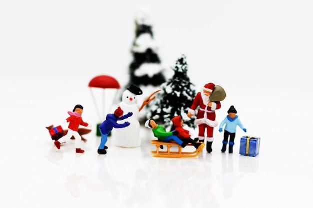 Miniaturowe osoby: dzieci bawią się z mikołajem i bałwanem.