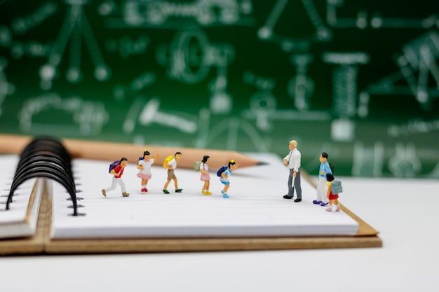 Miniaturowe osoby: dzieci ze szkolną torbą stojącą na książce z nauczycielem i szkołą