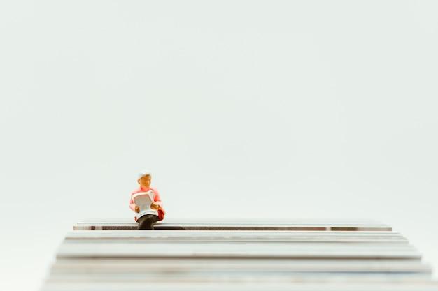 Miniaturowe osoby, kobieta siedzi na papierze za pomocą edukacji i wakacji