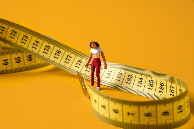 Miniaturowe osoby kobieta w labiryncie miarki pojęcie diety i odchudzania