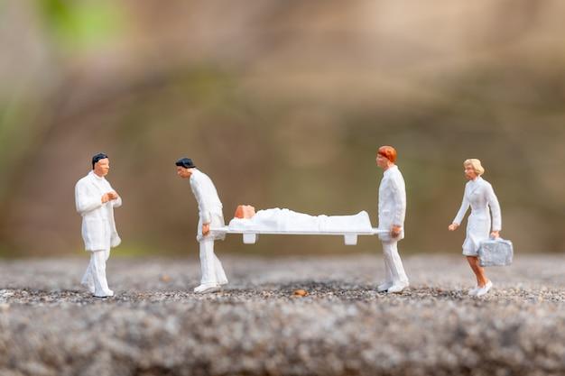 Miniaturowe osoby: lekarz z pielęgniarką niosą pacjenta na noszach.
