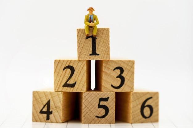Miniaturowe osoby: ludzie biznesu siedzą na drewnianym pudełku z numerem