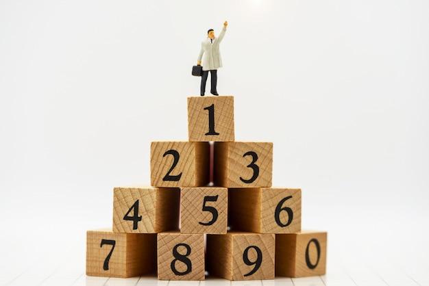 Miniaturowe osoby: ludzie biznesu stojący na drewnianym pudełku z najwyższym rankingiem.