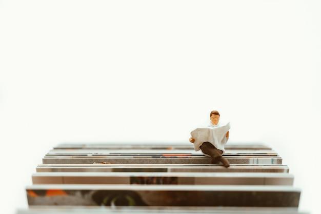 Miniaturowe osoby, mężczyzna siedzi na papierze za pomocą edukacji i wakacji