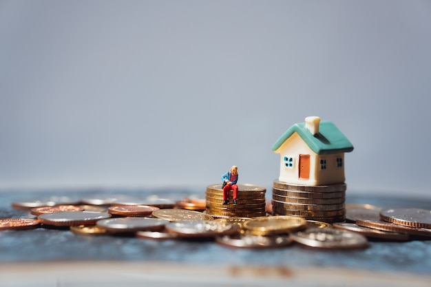 Miniaturowe osoby, młoda kobieta siedzi na stosie monet