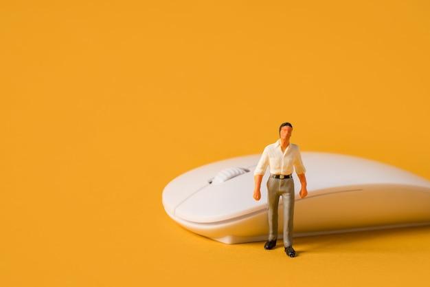 Miniaturowe osoby na żółtym tle męski programista lub biznesmen