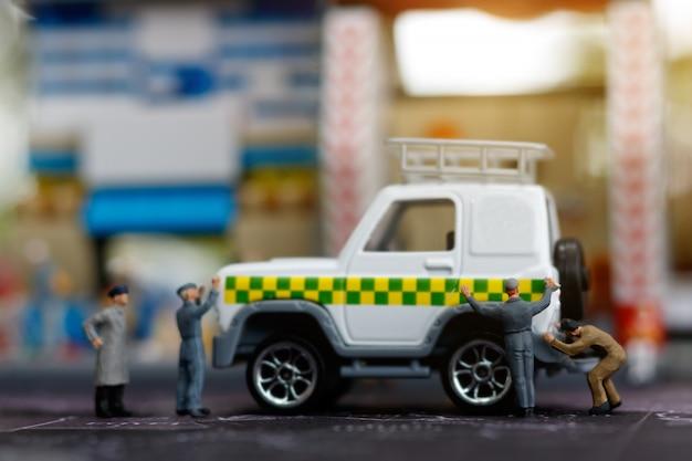 Miniaturowe osoby naprawiające samochód