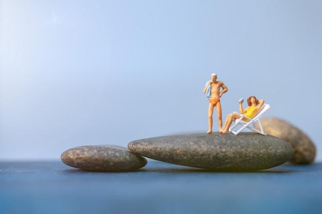 Miniaturowe osoby opalające się na plaży, koncepcja czasu letniego