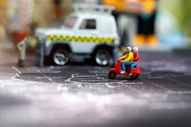 Miniaturowe osoby: para podróżników jadąca na motocyklowej ulicy miasta.