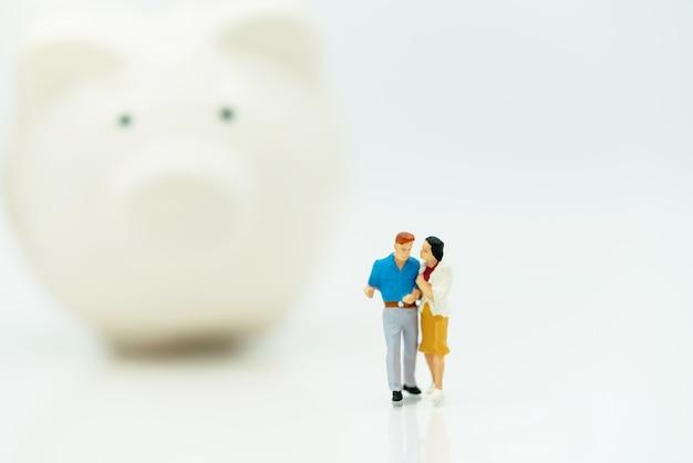 Miniaturowe osoby: para stojąca z skarbonką.
