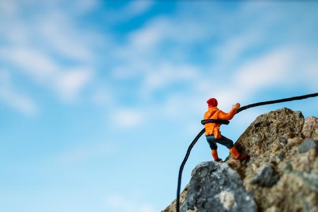 Miniaturowe osoby: pieszych wspinających się na skale. koncepcja sportu i rekreacji.