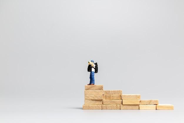 Miniaturowe osoby podróżujące stojąc na drewnianym bloku na szarym tle. koncepcja podróży i przygód