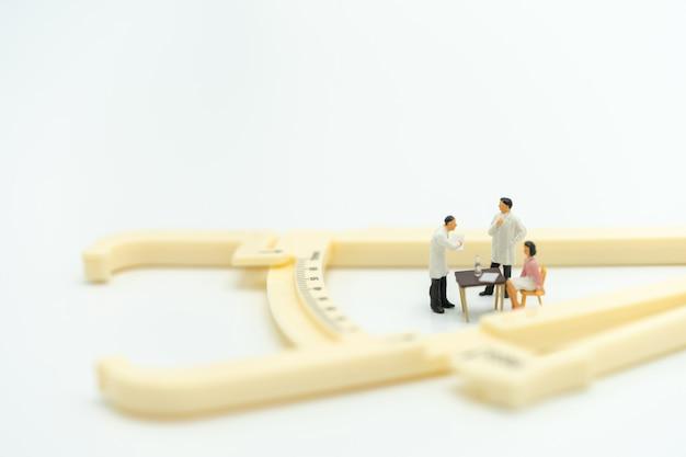 Miniaturowe osoby poproś lekarza, aby poprosił o problemy zdrowotne
