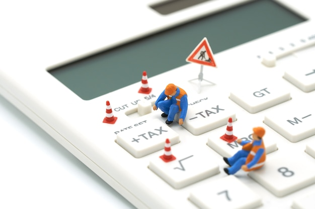 Miniaturowe osoby pracownik budowlany klawiatura przycisk tax do obliczenia podatku.