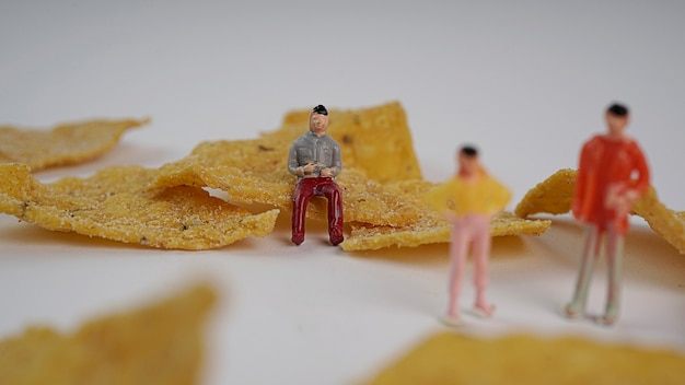Miniaturowe osoby pracujące lub siedzące wokół chipsów kukurydzianych z chipsami tortilla?