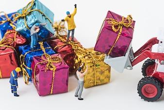 Miniaturowe osoby przygotowują się do transportu pudełka