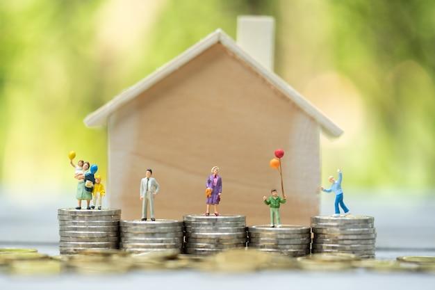 Miniaturowe osoby: rodzina stojąca na stosach monet z modelem domu na najwyższym stosie. koncepcje. koncepcja drabiny nieruchomości, hipoteki, inwestycji w nieruchomości, pieniędzy, miłości i walentynek.