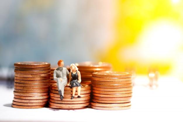 Miniaturowe osoby siedzące na kroku monety pieniędzy