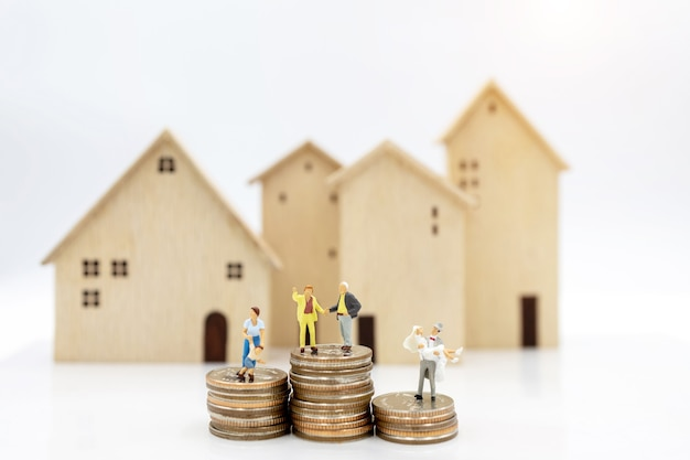 Miniaturowe osoby: starsza osoba stojąca na stosie monet z domu, koncepcja planowania emerytury.