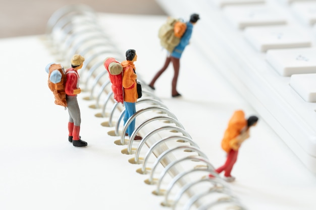 Miniaturowe osoby stoją na chodniku na początku podróży