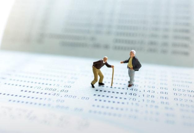 Miniaturowe osoby stoją na książeczce bankowej i stosie monet, koncepcje emerytalne.
