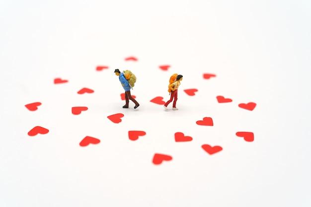 Miniaturowe osoby stojące z czerwonym papierem w kształcie serca. czerwone serce to obietnica miłości.