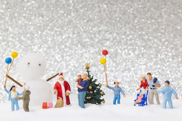 Miniaturowe osoby: święty mikołaj i dzieci na tle śniegu