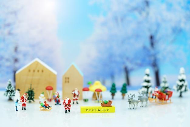 Miniaturowe osoby: święty mikołaj z dziećmi bawiący się śniegiem i choinką.