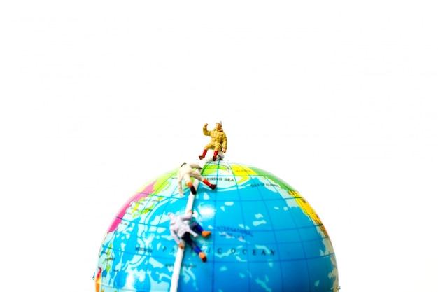 Miniaturowe osoby: turystów wspinających się na globe