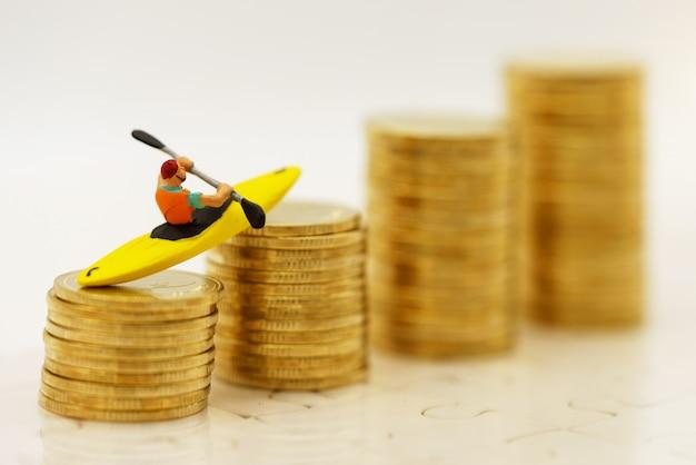 Miniaturowe osoby wiosło kajakowe na stosie złotych monet. finanse