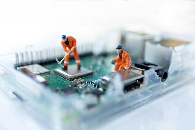 Miniaturowe osoby wyszukujące lub sprawdzające błędy i problem na mikroczipie, płycie głównej komputera.