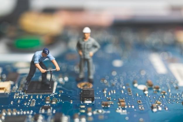 Miniaturowe osoby: zespół pracowników inżynierów naprawy komputera klawiatury laptopa