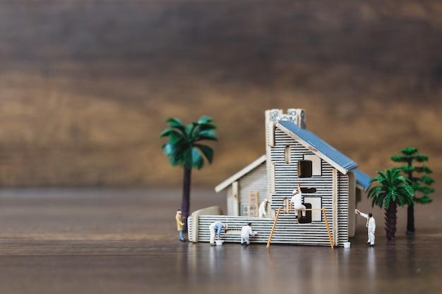 Miniaturowe osoby: zespół pracowników malujący nowy dom.