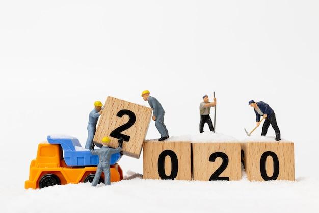 Miniaturowe osoby, zespół pracowników tworzą drewniany blok o numerze 2020