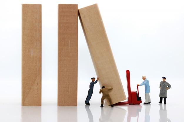 Miniaturowe osoby: zespół pracowników zatrzymujący efekt domina.