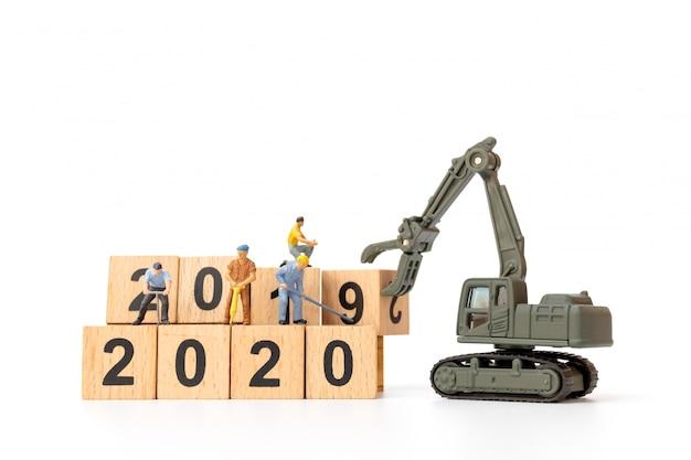 Miniaturowe osoby: zespół robotników tworzy drewniany blok o numerze 2020