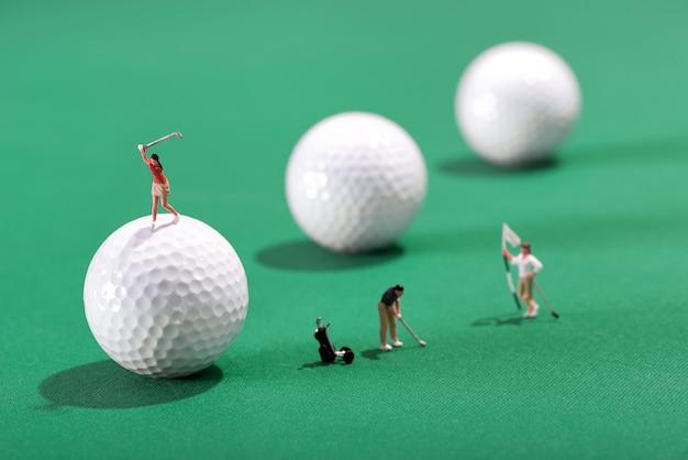 Miniaturowe postacie golfistów grających w golfa