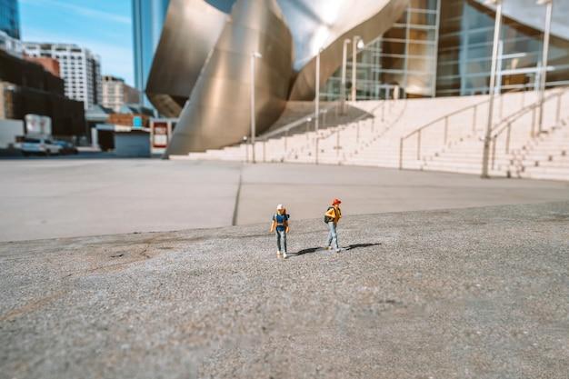 Miniaturowe postacie ludzi z plecakami na stoisku przed salą koncertową walta disneya