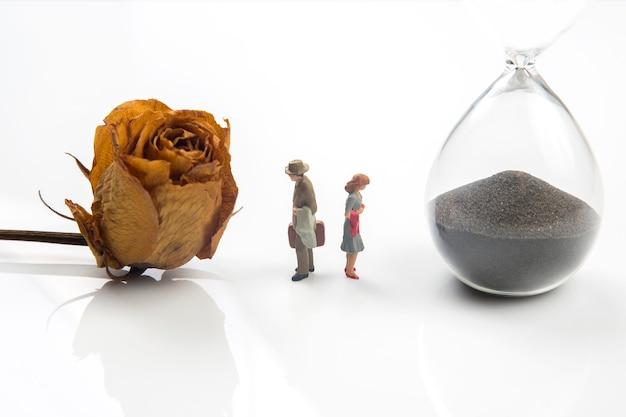 Miniaturowe postacie rozstające się z piaskowym zegarem i suszoną różą na białym tle.