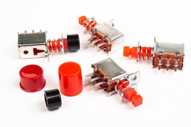 Miniaturowe przełączniki elektryczne z czerwonymi nasadkami na na białym tle biały
