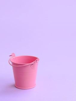 Miniaturowe puste różowe wiadro leży na fioletowym pastelowym tle