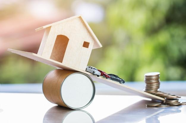 Miniaturowe samochody, dom na desce spadają z drogi. to jak nieformalne finansowanie kredytów dłużnych lub awaria własności spowodowana nadprodukcją