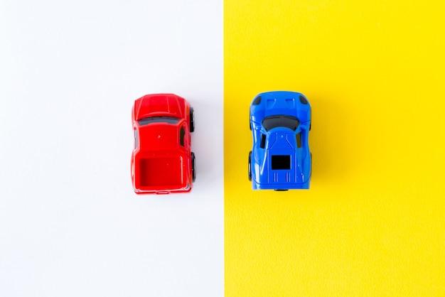 Miniaturowe samochodziki na żółtym widoku z góry