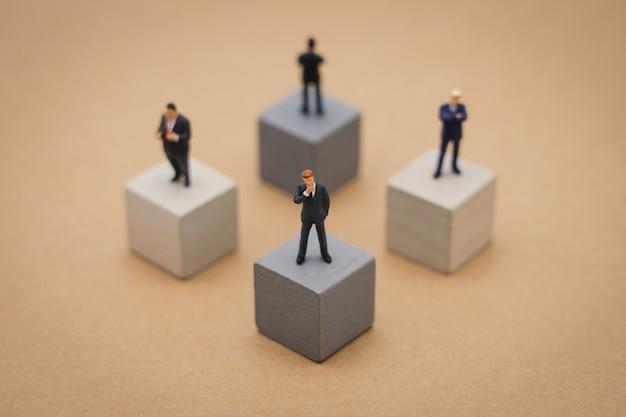 Miniaturowi 4 ludzie biznesmenów stoi na drewnianej sześcian inwestorskiej analizie