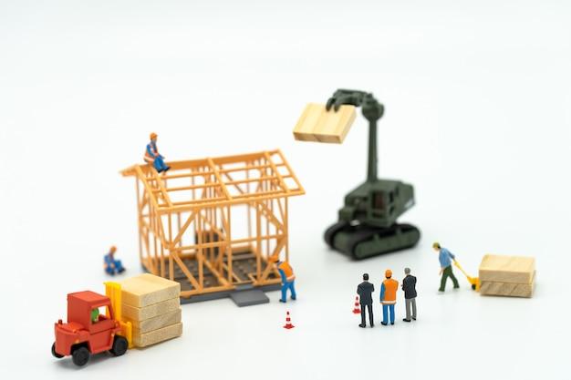 Miniaturowi biznesmeni stoi inwestyci analizy mieszkalnictwo lub inwestycję