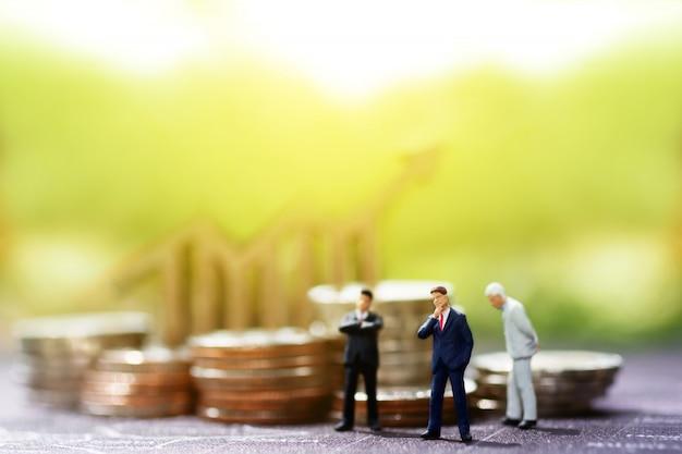 Miniaturowi biznesmeni stoi z wykresu i monet stosem.